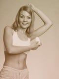Girl applying stick deodorant in armpit. Stock Image