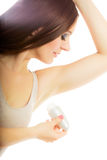 Girl applying stick deodorant in armpit. Royalty Free Stock Images