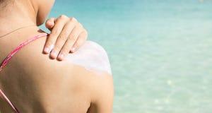 Girl applying sun lotion on the beach Royalty Free Stock Photography