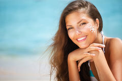 Girl applying Sun Tan Cream. Beautiful happy Girl applying Sun Tan Cream on her Face Royalty Free Stock Image