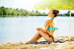 Girl applying sun tan cream on her skin Stock Photo