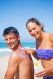 Girl applying sunblock cream on a father's back. Stock Photos