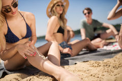 Girl applying suntan cream. A photo of young women sitting on the beach with her friends and applying a suntan cream on Stock Photography