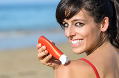 Girl applying suntan lotion in shoulder Royalty Free Stock Image