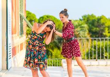 Sneak attack. A girl approaching another girl from behind and attacking her from the back. Surprise attack and hair pulling. Girl fight stock image