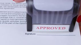 Girl approves a document for collaboration and puts a stamp. Close up stock video