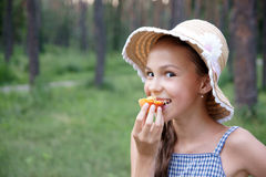 Girl with apricot. Portrait of preteen girl in straw hat eats apricot on green leaves background outdoors in park Royalty Free Stock Photography