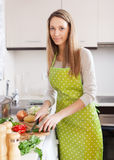 Girl in apron cooking with vegetables. At domestic kitchen Stock Photos