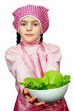 Girl in an apron with the dish of lettuce Royalty Free Stock Photo