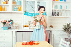Girl apron with flowers in the kitchen. Stock Image
