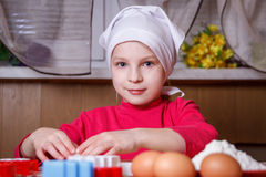Girl in apron making cookies in kitchen Royalty Free Stock Photos