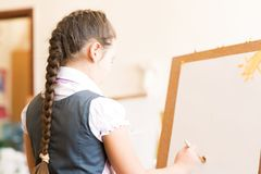 Girl in apron painting Stock Images