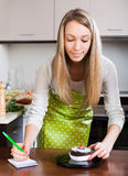 Girl in apron weighing cakes Stock Photography