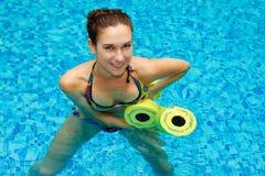 Girl in aqua fitness  aerobic. Aqua aerobic, woman in water with dumbbells Stock Image