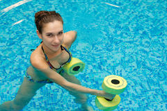 Girl in aqua fitness aerobic. Aqua aerobic, woman in water with dumbbells Royalty Free Stock Photography