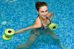 Girl in aqua fitness aerobic. Aqua aerobic, woman in water with dumbbells Stock Photos