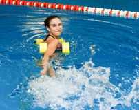 Girl in aqua fitness aerobic. Aqua aerobic, woman in water with dumbbells splashes water Royalty Free Stock Photography