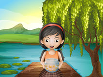 A girl with an aquarium standing at the riverbank Stock Images