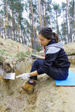 The girl-archaeologist cleans a wall excavation Royalty Free Stock Photos