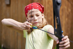 Girl archer with bow shooting to sport aim Stock Photo