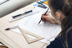 Girl architect draws a plan, design, geometric shapes by pencil on large sheet of paper at office desk. Stock Photo