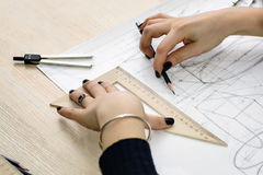 Girl architect draws a plan, design, geometric shapes by pencil on large sheet of paper at office desk. Royalty Free Stock Photo