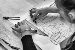 Girl architect draws a plan, design, geometric shapes by pencil on large sheet of paper at office desk. Stock Images