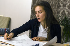 Girl architect draws a plan, design, geometric shapes by pencil on large sheet of paper at office desk. Stock Image