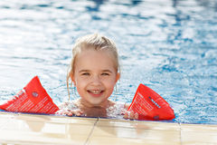 The girl in the arm ruffles in the pool smiling.  Stock Images