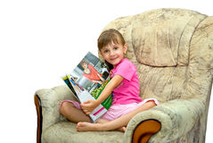 The girl in an armchair. The girl sits in an armchair with magazine Royalty Free Stock Image