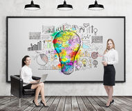 Girl in armchair and blond girl near light bulb sketch. Girl with laptop sitting near whiteboard with giant light bulb sketch surrounded by graphs. Her colleague Royalty Free Stock Photography