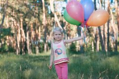 Girl with an armful of balloons in forest Stock Photography