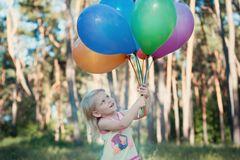 Girl with an armful of balloons Royalty Free Stock Image