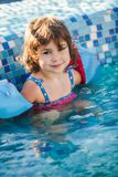 Girl in armlets the swimming pool. Two years old girl in armlets the swimming pool royalty free stock photos