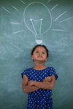 Girl with arms crossed standing by bulb drawing on wall. Girl with arms crossed standing by bulb drawing on gray wall stock photography