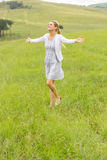 Girl arms outstretched grassland Stock Photo