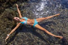Girl with arms outstretched and legs apart lies on water. Young woman swims on back with spread her arms and legs in sea royalty free stock images