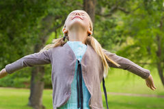 Girl with arms outstretched looking upwards at park Stock Photography
