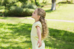 Girl with arms outstretched looking upwards at park Royalty Free Stock Photo