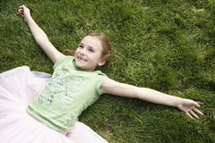 Girl With Arms Outstretched Lying On Grass Stock Photos