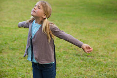 Girl with arms outstretched at park Stock Photo