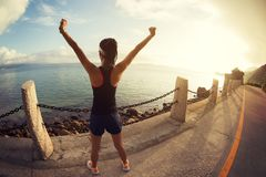 Girl with arms outstretched at a seaside. Beautiful inspiring landscape and sea with girl and hands raised on sunrise Royalty Free Stock Images