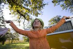 Girl (9-11) with arms raised by camper van in field, smiling, low angle view Royalty Free Stock Photo