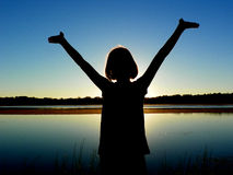 Girl with Arms Raised by Lake. A silhouette of a girl with her arms raised to heaven standing in front of a lake stock photo