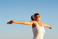 Girl with arms raised towards the sky Stock Photos