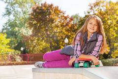 Girl with arms on red skateboard at autumn time Stock Images
