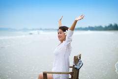 Girl with arms wide open on chair at beach Royalty Free Stock Photography