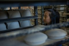 Girl arranging cups in shelf. At pottery workshop stock image