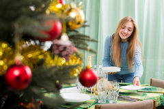 Girl arranging decorations of Christmass tree Stock Photo