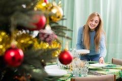 Girl arranging decorations of Christmass tree. Smiling blonde girl arranging decorations of Christmass tree Stock Photo